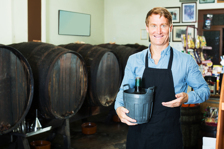 Smiling man working in winery wearing apron holding big bottle of wine in plastic bucket