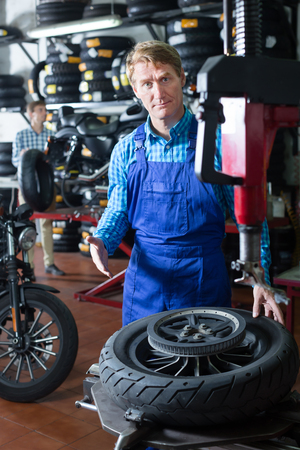 Attentive adult mechanic man standing with motorcycle wheel in shop