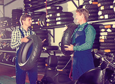 Two happy technician standing with new tires for motorcycle in hands in shop