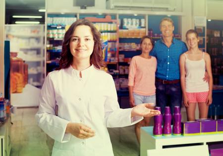 portrait of glad european female druggist in white coat working in pharmacy Imagens