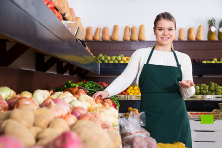 Young female seller in apron offering fresh greens and vegetables on the supermarket