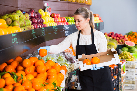 Portrait de jeune vendeuse expose les fruits de la boîte au supermarché Banque d'images