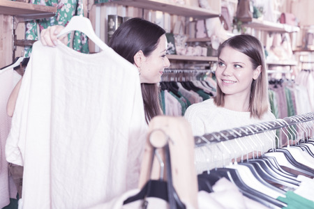 Positive young women buyers choosing pullover in the fashion store