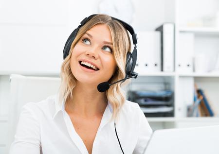 Młoda dziewczyna w call center ze słuchawkami siedząca z laptopem