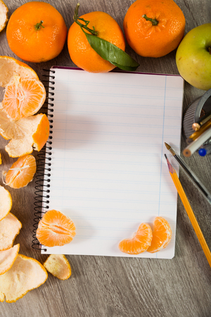 Notebook in range with writing utensils surrounded by fruit