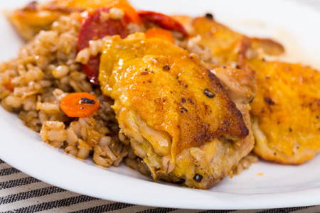 Closeup  of tasty  chicken thighs with pearl barley  at plate on table 스톡 콘텐츠