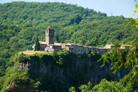 View of Castellfollit de la Roca, medieval Catalan hamlet on cliff in summer day