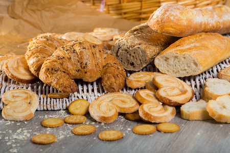 Various bakery and pastry products on rattan mat on wooden table