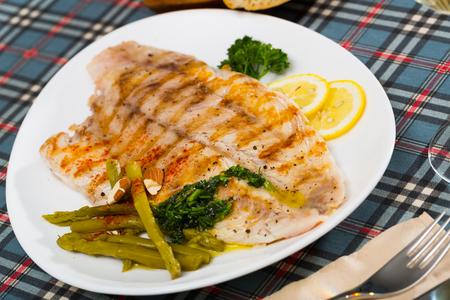 Delizioso pesce persico alla griglia con contorno di verdure di asparagi marinati e fette di limone su piatto bianco Archivio Fotografico