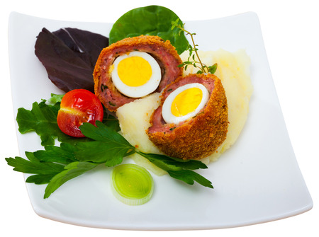 Hard-boiled quail egg wrapped in sausage meat, breaded and fried (Scotch egg) served with pureed potatoes, baked carrots, cherry tomatoes and greens. Isolated over white background