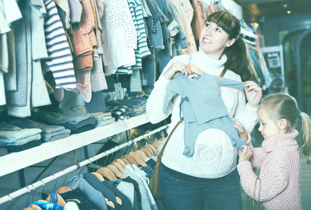 Smiling pregnant mother and daughter examining romper suits for baby in children's cloths store. Focus on girl