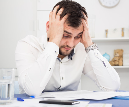 Young man struggling to pay utility bills and rent for his apartment