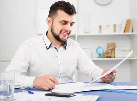 Young male preparing to signing financial agreement at home