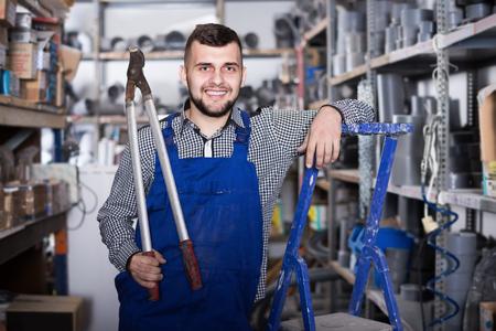Lächelnder Mann Arbeiter zeigt verschiedene Instrumente am Arbeitsplatz Standard-Bild