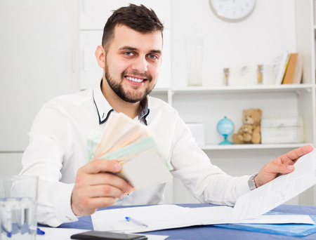 Smiling man worker earning money effectively online at home Stock Photo
