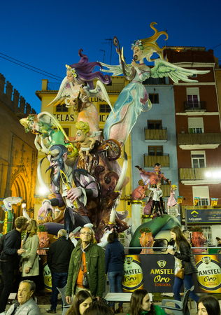 VALENCIA, SPAIN - MARCH 18, 2019: Giant colorful artistic monument (falla) created of comic figures (ninots) for parade on city streets during traditional Falles celebration Editorial