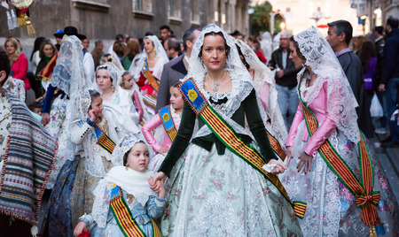 VALENCIA, SPAIN - MARCH 18, 2019: Falleres in colorful historic dresses parading through city streets during traditional Falles celebration