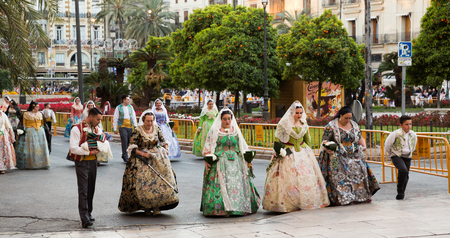 VALENCIA, SPAIN - MARCH 18, 2019: People in Spanish national costumes walking through streets of Valencia during Falles