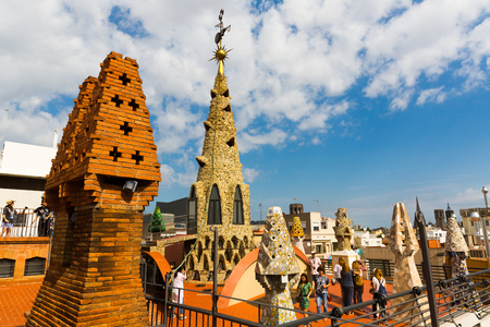 BARCELONA, SPAIN - SEPTEMBER 02, 2018: Fantastic shapes fo chimneys and central spire on roof of Guell Palace by Antoni Gaudi 新闻类图片