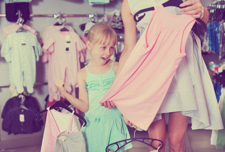 Little girl looking at colored dress and surprised