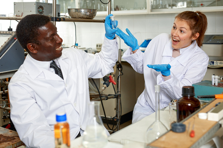 Happy male and female scientists looking for result after chemical experiment