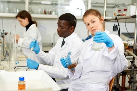 Fokussierte Labortechnikerinnen in Gläsern, die mit Reagenzien und Reagenzgläsern arbeiten, Mann im Hintergrund Standard-Bild
