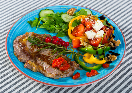 Delicious fried beef loin with healthy summer salad of arugula with fresh vegetables, soft cheese and walnuts