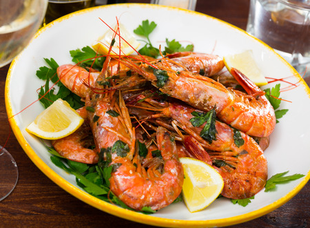 Appetizing fried shrimps with lemon and parsley