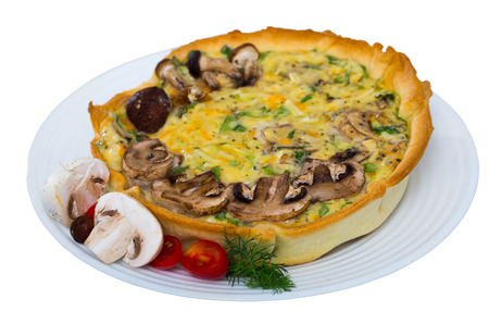 Traditional french homemade quiche lorraine with mushrooms, cheese and greens. Isolated over white background