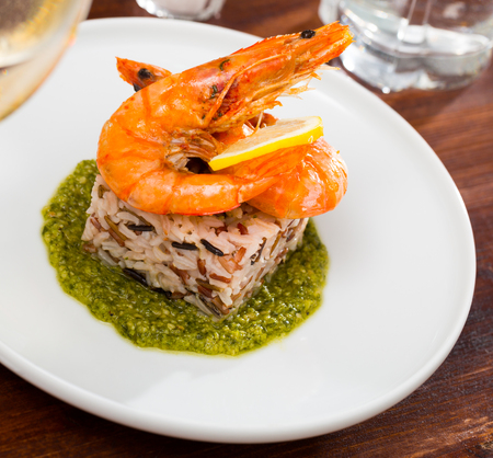 Dish of Mediterranean cuisine – baked in oven tiger shrimps on rice pillow