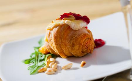 Delicioso postre: camembert sobre un mini croissant servido con mermelada de frambuesa