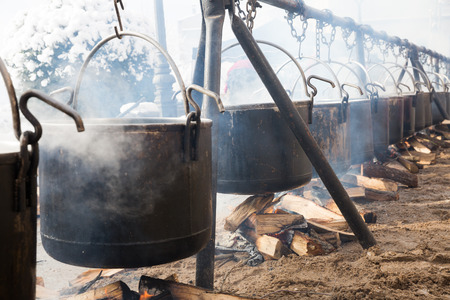 View of iron cauldrons for cooking outdoors in medieval style in open fire