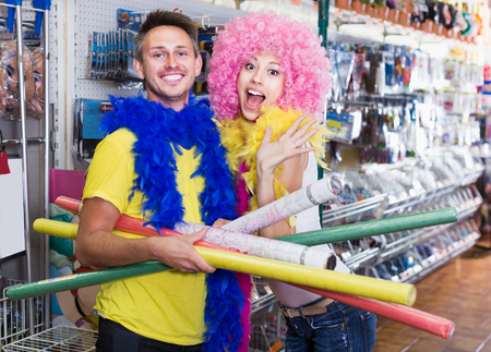 Pair of young positive people having fun in festive accessories shop