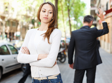 Offended girl on departing boyfriend background after quarrel outdoors Stockfoto