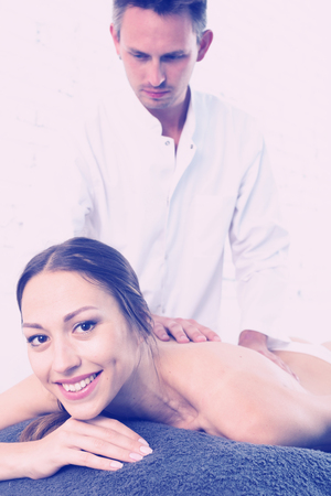 Relaxing professional massage for young woman in spa salon 免版税图像