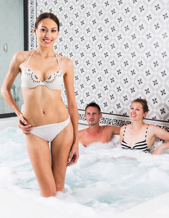 Portrait of happy woman enjoying and relaxing in jacuzzi at spa complex