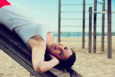 Young smiling woman doing exercises on beach by ocean at daytime