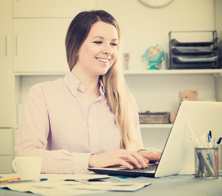 Smiling young employee working effectively on project in office