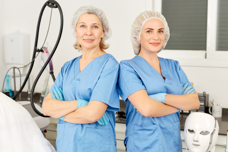 Portrait of qualified females cosmetologists smiling confidently in medical center Stock Photo