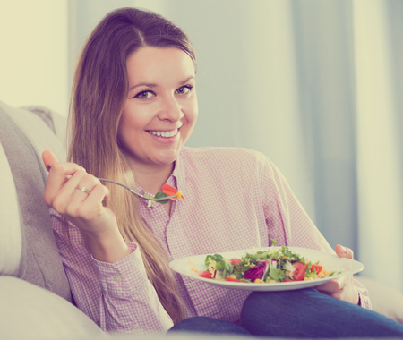Young smiling woman enjoying to eat tasty green salad at home