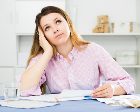 Positive young girl preparing agreement papers about finances at home