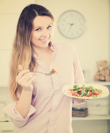 Smiling young woman tasting fresh green salad with pleasure at home