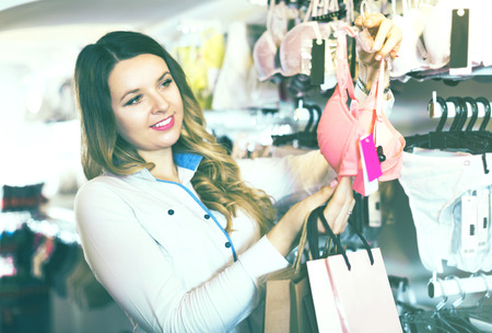 Young female customer choosing pretty bra in lingerie shop Stock Photo