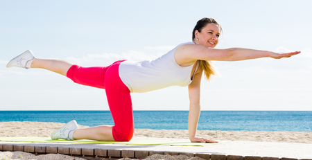 Young woman doing yoga poses sitting on sunny beach by ocean in morning Stock Photo