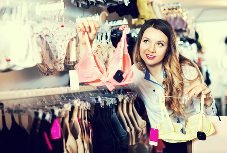 Young attractive woman choosing pretty bra in lingerie shop Stock Photo