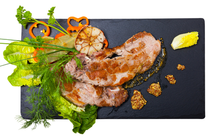 Image of cooked fried pork meat with different herbs served  on black plate. Isolated over white background