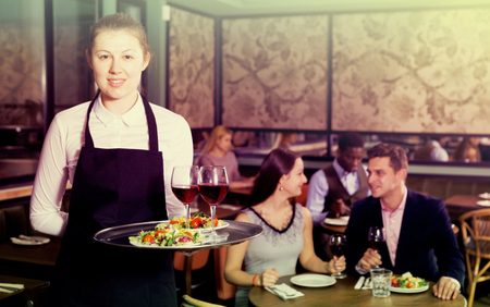 Portrait of smiling waitress with serving tray meeting restaurant guests Stockfoto