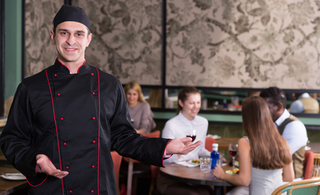 Portrait of confident smiling chef standing in restaurant hall with welcome gesture