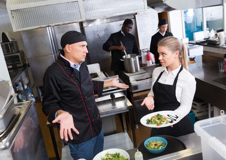 Bewildered chef making helpless gesture while talking with surprised waitress pointing to cooked dish