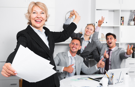Happy team with businesswoman on foreground emotionally gesturing and celebrating victory at office